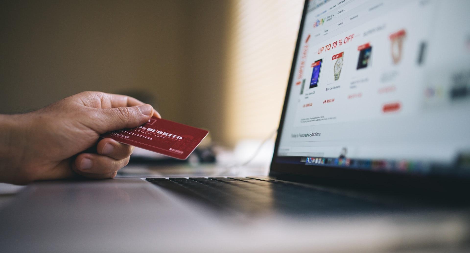 Osoba płaci kartą zazakupy internetowe - poszybkiej odpowiedzi nazapytanie.